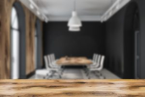 Modern meeting room interior with black walls, tiled floor and long wooden table with white chairs. A mental health counselor is preparing for a therapy workshop in Indianapolis, IN at Northside Mental Health